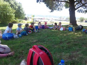 Les enfants pique-niquent à l'ombre, sous les arbres.
